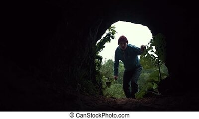Young hiker enters to dark cave under low stone vault and walk into darkness