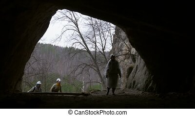 Young hiker in helmet enters to the dark cave with...
