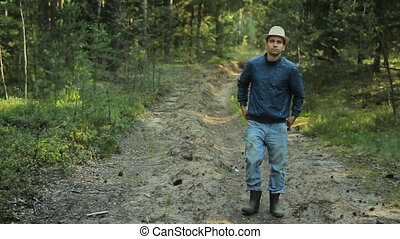 Young hiker man with hat walking in forest. He adjusts his old jeans and goes on