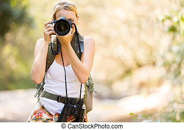 young hiker taking photos in mountain valley