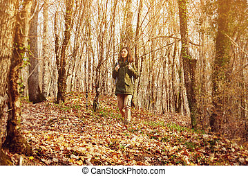 Young hiker woman walking in autumn forest