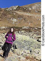 Young hiker woman walking on mountain