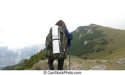 Young hiker woman with backpack walking up the mountain on the stony slope reaching the top