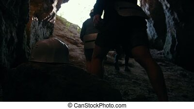 Young hikers in helmets climbing up from the dark cave,...