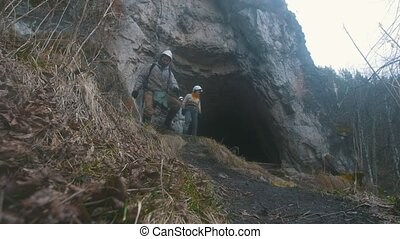 Young hikers in helmets coming out from the dark cave with...