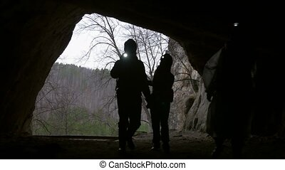 Young hikers silhouette in helmet enters from the forest to the dark cave with flashlight