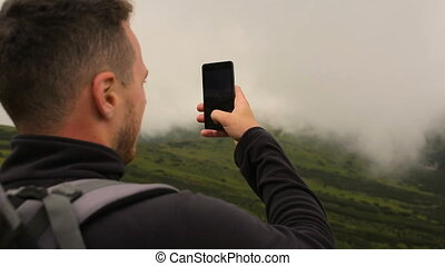 Young hikers taking photo with smart phone in the mountains