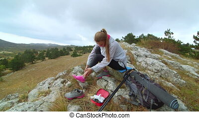 Young hiking woman holding ankle with pain in the mountains using first aid kit