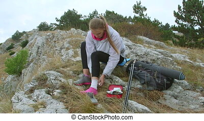 Young hiking woman sprained ankle using first aid kit in the...