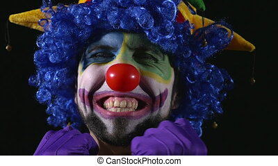 Young hilarious clown making funny faces
