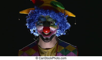 Young hilarious evil clown making scary faces