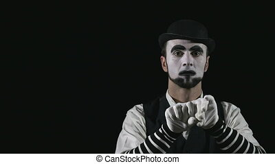 Young hilarious mime making funny facial expressions