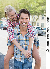 Young hip man giving his blonde girlfriend a piggy back on a...