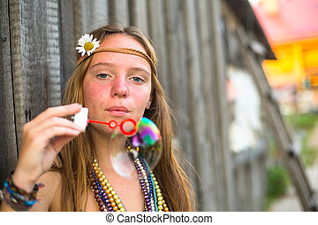 Young hippie girl blows soap bubbles on a street in the countryside.