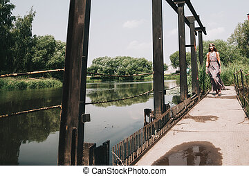 young hippie woman walking on wooden bridge