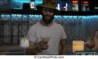 Young hipster bearded man flirting and tasting a delicious cocktail in a fancy bar night out with friends