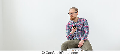 Young hipster bearded man sitting over the white background with copy space