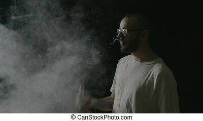 Young hipster boy with glasses vaping from a vaporizer and...