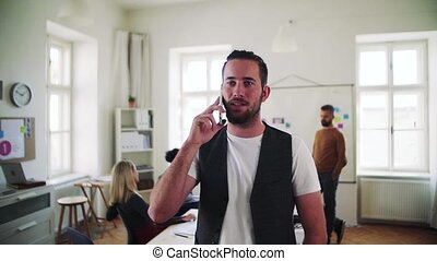 Young hipster businessman with smartphone working in a...