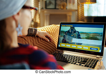 young hipster buying bus tickets online on laptop