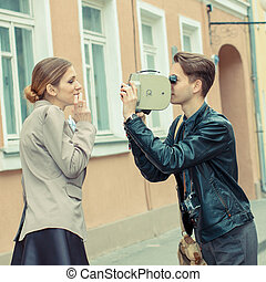 young hipster couple doing a film on vintage movie camera on the streets of European city