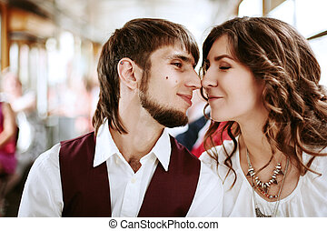 Young hipster couple kissing in the bus