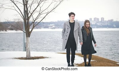Young hipster couple walking hand in hand by the riverside