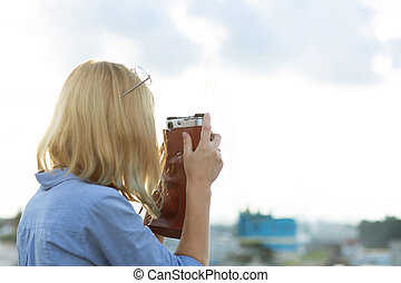 Young hipster girl photographer in blue shirt taking pictures on a vintage film camera. Space for text