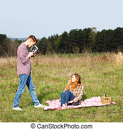 young hipster guy photographs the girl on a vintage camera
