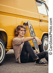hipster guy sitting next his yellow car during road trip