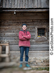 young hipster in front of wooden house