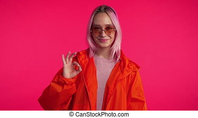 Young hipster making OK sign over pink background. Winner. Success. Positive girl smiles to camera. Body language. Slow motion.