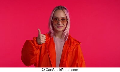 Young hipster making thumbs up sign over pink background. Winner. Success. Positive girl smiles to camera. Body language.
