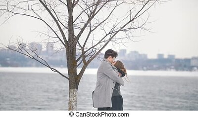 Young hipster man and woman embracing under the tree by the...