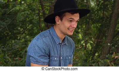 Young hipster man in hat laughing, relaxed in front of the camera