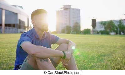 man sitting on grass in city park
