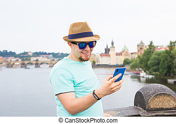 Young hipster man using mobile smart phone outdoor