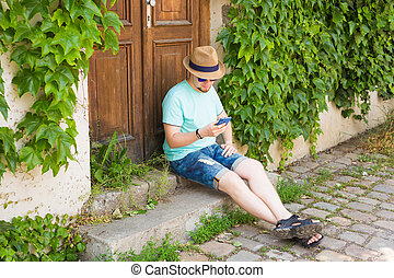 Young hipster man using mobile smart phone outdoors