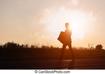 Young hipster man walking with suitcase in hand at sunset
