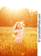 Young hipster model beauty woman, blowing Long Hair. Casual Girl in the field in Sunset in spring or summer landscape background. Springtime. Summertime. Allergic to pollen of flowers. Allergy. Backlit. Sun Light. Autumn. Glow Sun, Sunshine