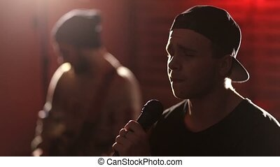 Young hipster singing into microphone on stage