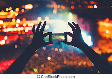 young hipster taking photos and videos at concert. Modern ...