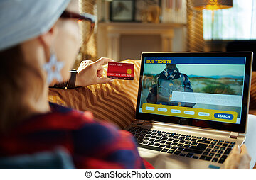 young hipster with credit card buying bus tickets online