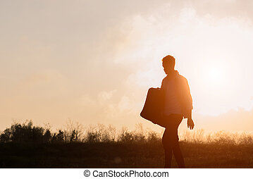 Young hipster with suitcase in hand at sunset