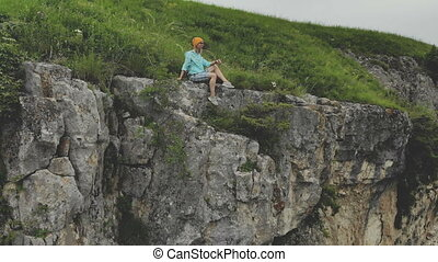 Young hipster woman is sitting on the edge on the grass of...