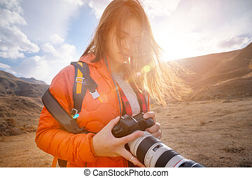 Young hipster woman with a camera in her hands in the mountains in backlight. Hair fluttering in the wind