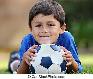 Young hispanic boy lying down with soccer ball