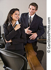 Young Hispanic businesswoman with male colleague in boardroom