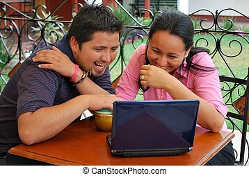 Young Hispanic couple laughing together as they look at a...