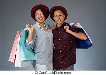 Young hispanic couple with shopping bags